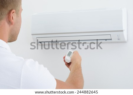 Man Operating Air Conditioner With Remote Controller - stock photo