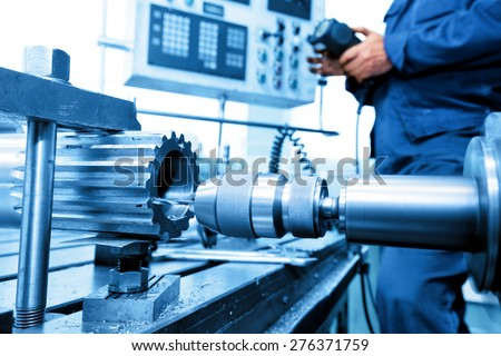 Man operating CNC drilling and boring machine in workshop. Industry, industrial concept. - stock photo