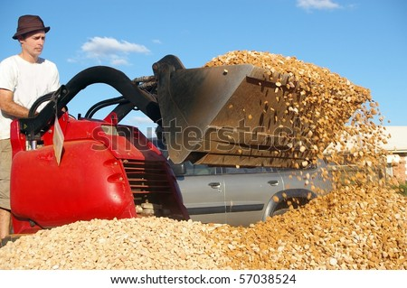 man operating small earth moving machine on gravel - stock photo
