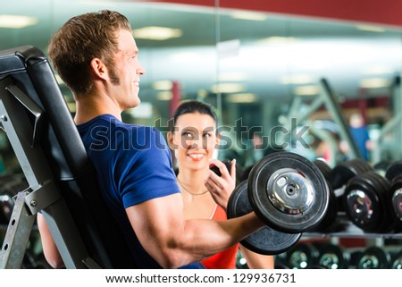 Man or Bodybuilder with his personal fitness trainer in the gym exercising sport with dumbbells, closeup - stock photo