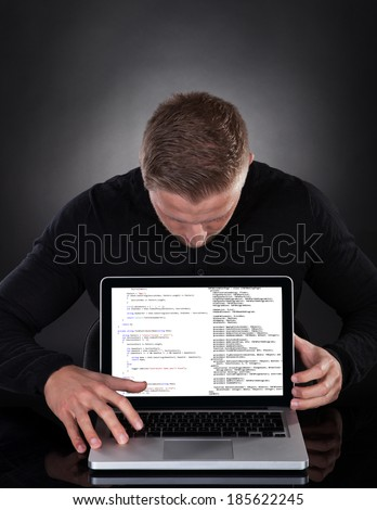 Man or hacker stealing data from a laptop at night bending forwards over the keyboard in the glow from the screen as he browses the internet or retrieves and downloads personal data - stock photo