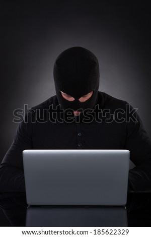 Man or hacker working on a laptop computer at night bending forwards over the keyboard in the glow from the screen as he browses the internet or retrieves and downloads personal data - stock photo