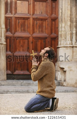 Man or monk praying in front of the church holding a cross - stock photo