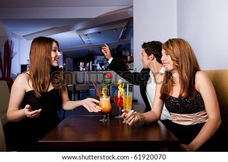 Man ordering drinks while girls having fun - stock photo