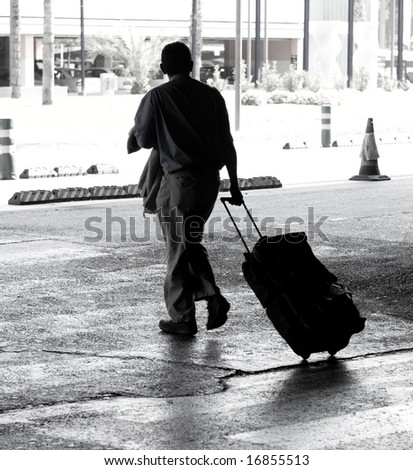 Man out of the airport on the crosswalk - stock photo