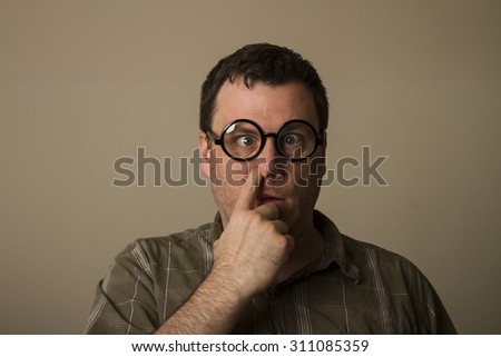 Man out there with crossed eyes and glasses picking his nose - stock photo