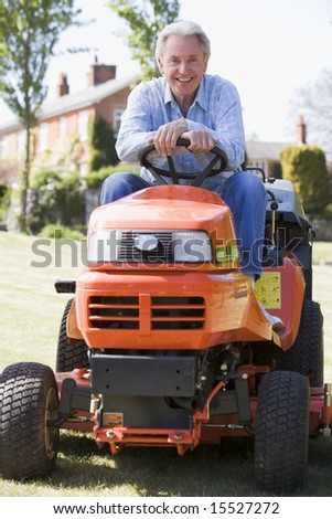 Man outdoors on lawnmower smiling - stock photo