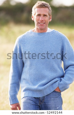 Man Outdoors Walking In Autumn Landscape - stock photo
