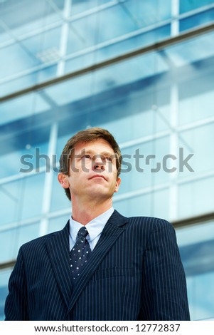 Man outside office building, looking up - stock photo