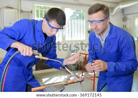 Man overseeing trainee working with blowtorch - stock photo