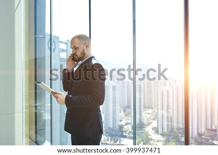 Man owner of prosperous real estate company with touch pad in hand is calling to his client to find out whether he accepted the decision to buy, while is standing in office near window with copy space - stock photo