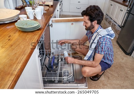 man packing dirty dishes into dishwashing machine in home kitchen - stock photo