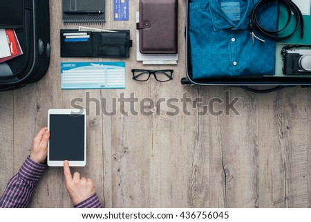 Man packing for a trip, he is using a digital touch screen tablet and booking flights online using a mobile app, flat lay banner