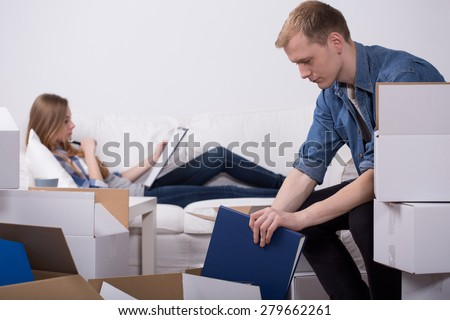 Man packing moving boxes and his lazy girlfriend - stock photo