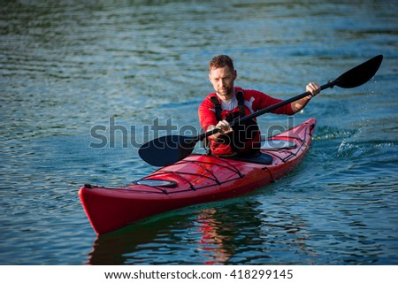 man paddles a red kayak on the pond near the shore, kayaking - stock photo