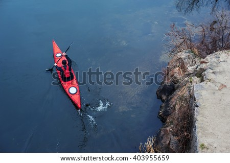 man paddles a red kayak on the river near the shore, kayaking - stock photo