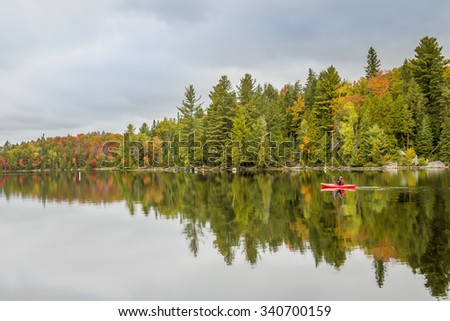 Man Paddling a Kayak in Autumn - Algonquin Provincial Park, Ontario, Canada - stock photo