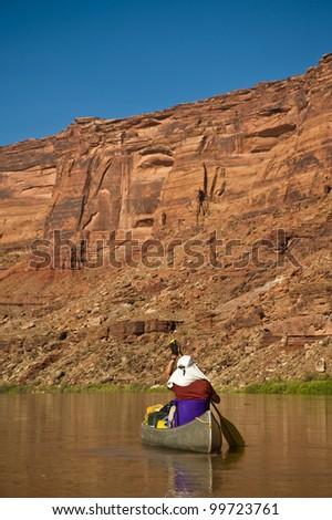 Man paddling canoe on Green River in Utah canyonlands - stock photo