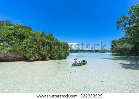 Man paddling his kayak on clear shallow water of a tropical lagoon, Ishigaki Island National Park of the Yaeyama Islands, Okinawa, Japan  - stock photo