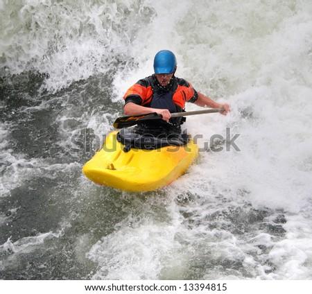 Man paddling his Kayak on Whitewater Rapids - stock photo