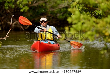 Man paddling in a red kayak in Florida - stock photo