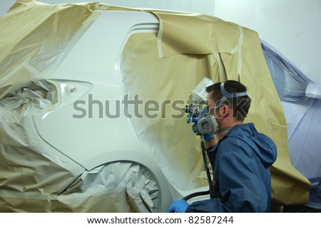 Man painting a car. - stock photo
