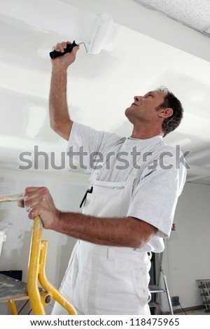 Man painting a ceiling white - stock photo