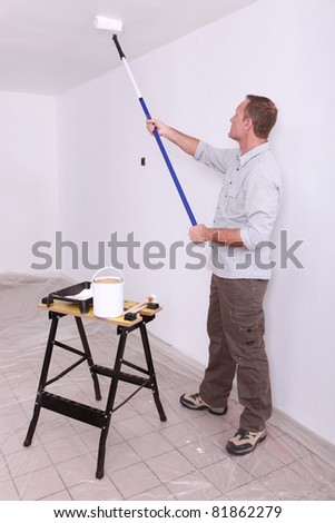 Man painting ceiling with roller - stock photo