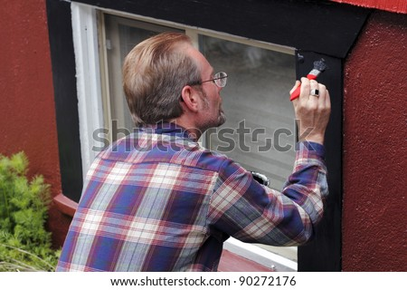 Man painting house window trim with black paint outdoors in the day.