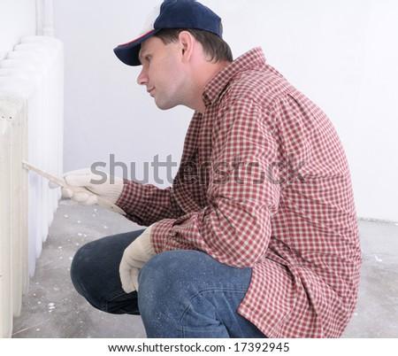Man painting radiator - stock photo