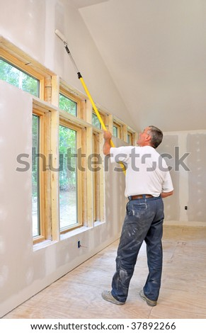 Man painting room with a roller - stock photo
