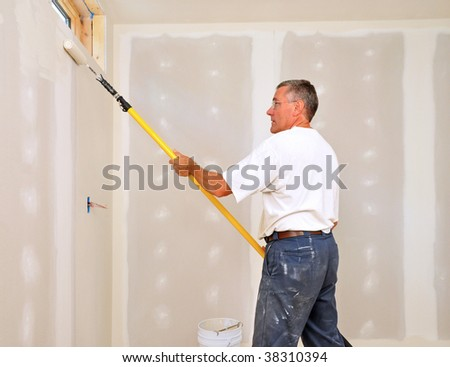 Man painting room with roller attached to an extension pole - stock photo