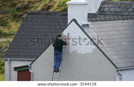 man painting the side of a house white - stock photo