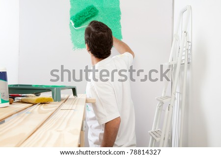 Man painting the wall with roller and brush, stepladder in background