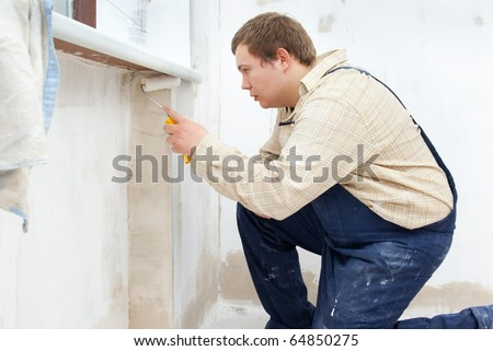 Man painting wall with roller - stock photo