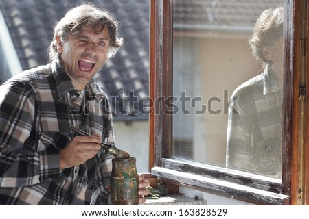 man painting windows - stock photo