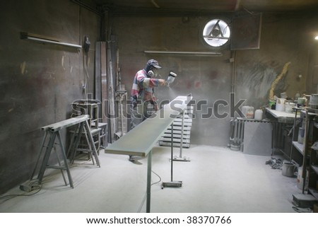 Man painting with spray paint gun in his home workshop