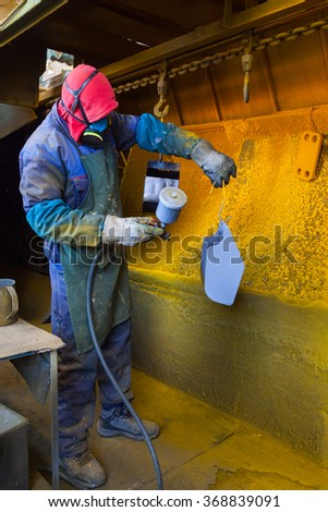 Man painting with spray paint gun in workshop