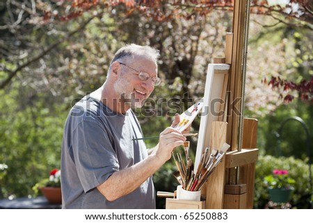 Man paints on an easel in a pleasant outdoor setting. - stock photo