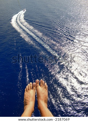 man parasailing over ocean with feet and boat in view - stock photo
