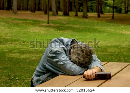 man passed out at picnic bench after drinking alcohol - stock photo