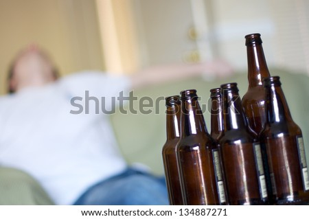 Man passed out on couch with empty beer bottles, angled - stock photo