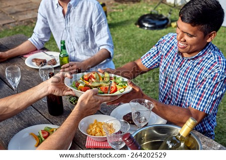 man passing dish healthy fresh salad at outdoor barbecue garden party gathering - stock photo
