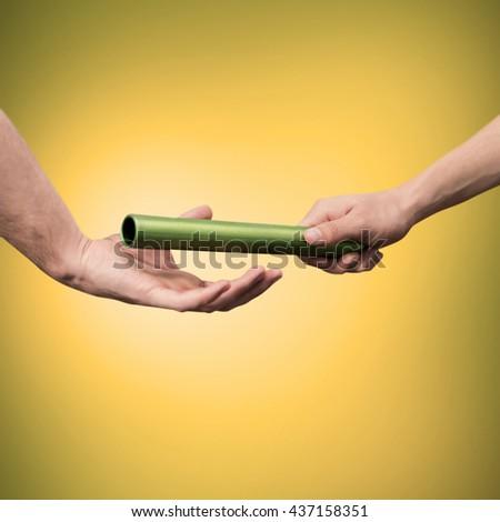 Man passing the baton to partner on yellow background - stock photo