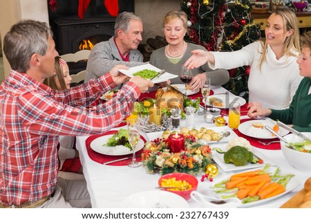 Man passing the plate to his wife at home in the living room - stock photo