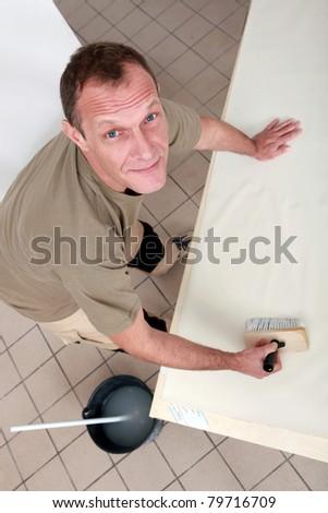Man pasting wallpaper - stock photo