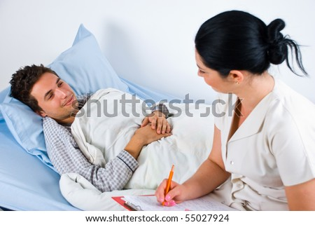 Man patient lying on bed in hospital and having an conversation with his doctor woman - stock photo