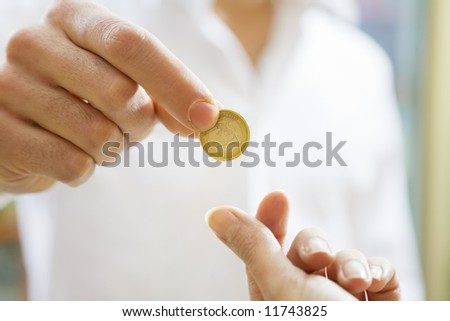 man paying 1 euro to the cashier in a store. Close up of the coin and some copy space - stock photo