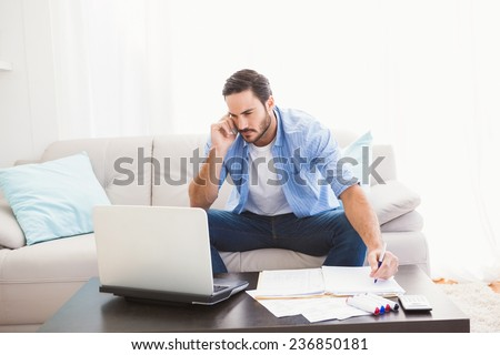 Man paying his bills with laptop while talking on phone in the living room - stock photo