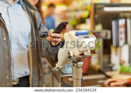 Man paying wireless with his smartphone at supermarket checkout - stock photo